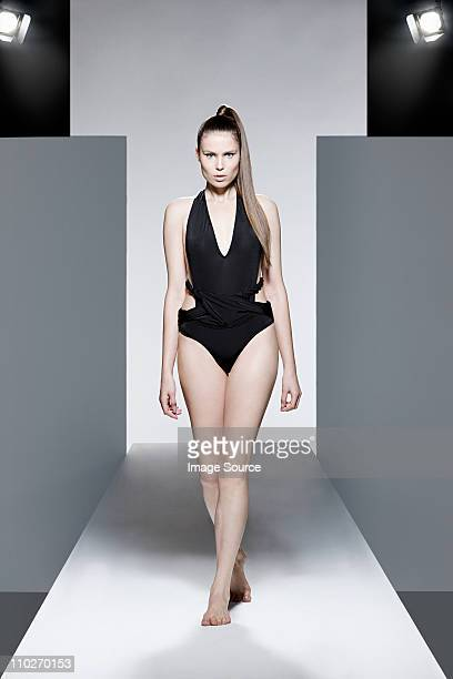 Model wearing black swimsuit on catwalk at fashion show