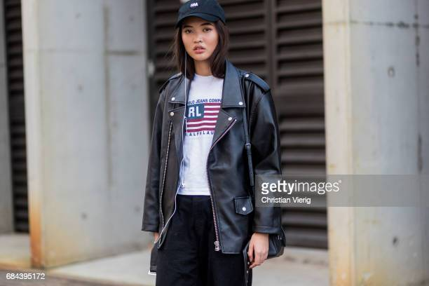 A model wearing cap leather jacket black cropped pants boots with print at day 5 during MercedesBenz Fashion Week Resort 18 Collections at...