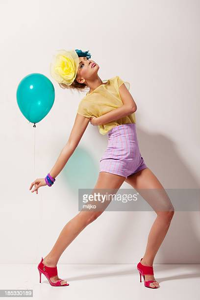 Model wearing happy outfit posing for a shot with a balloon