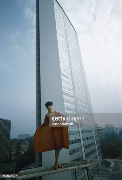 Model wearing red panelled cocktail dress by Italian designer Fabiani posing against backdrop of the Pirelli building skyscraper designed by Gio Ponti