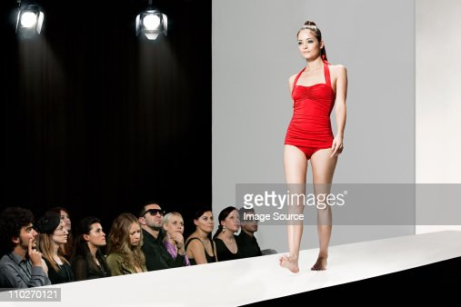Model wearing red swimsuit on catwalk at fashion show