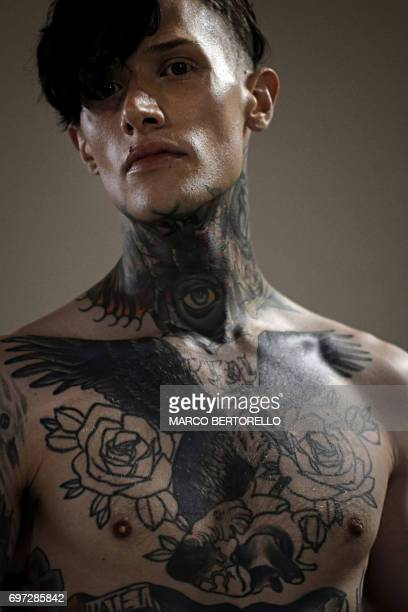 TOPSHOT A model wearing tattoos is pictured backstage before the show for fashion house Sulvam during the Men's Spring/Summer 2018 fashion shows in...