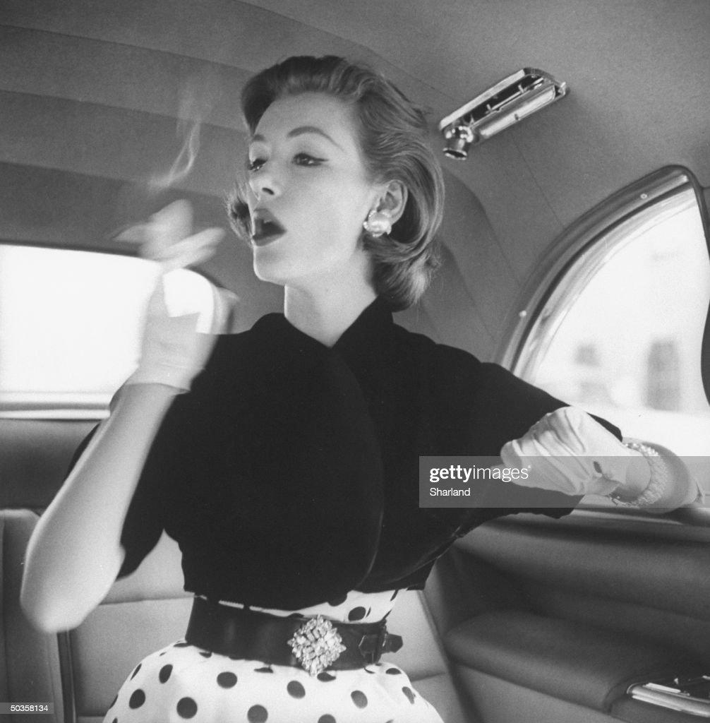 Model wearing velvet bolero jacket over polka-dotted sheath dress, smoking in back seat of automobile.