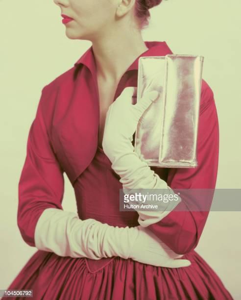 A model wearing white gloves holding a silver handbag circa 1950