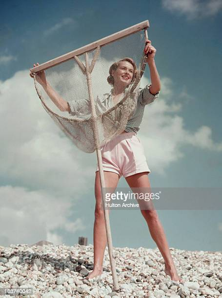 A model wearing white shorts and green gingham shirt poses with a fishing net on a pebble beach Great Britain circa 1955