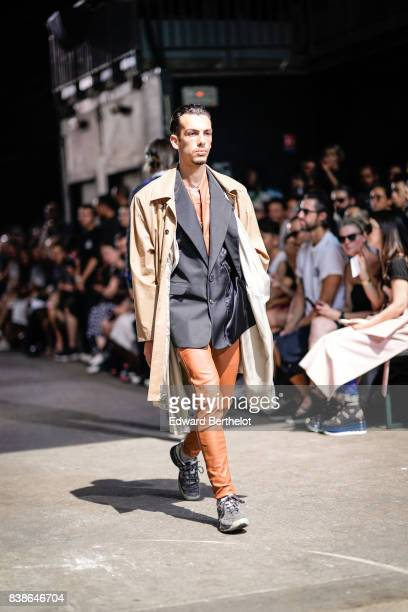 A model wears a beige trench coat a black suit jacket orange pants gray shoes outside the Y/Project show during Paris Fashion Week Menswear...