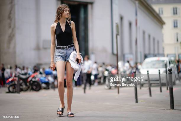 A model wears a black low neck sleeveless top blue denim shorts and sandals outside the 22/4 Hommes show during Paris Fashion Week Menswear...