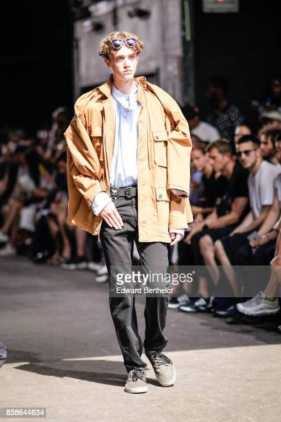 A model wears a blue shirt a yellow jacket black pants gray shoes outside the Y/Project show during Paris Fashion Week Menswear Spring/Summer 2018 on...