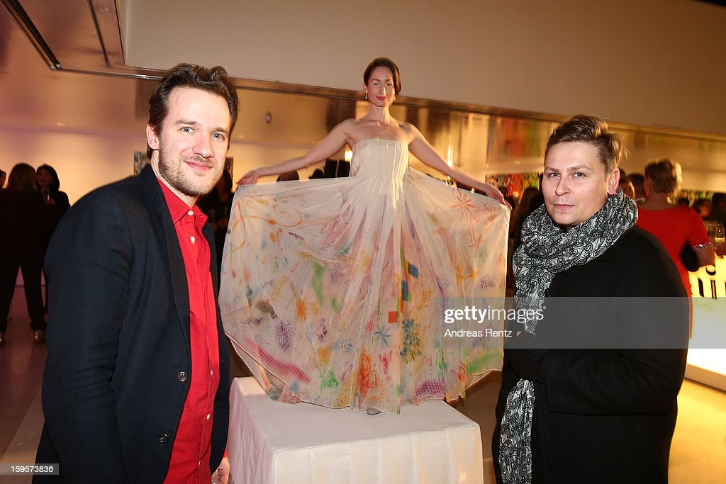 A model wears a Dawid Tomaszewski (R) dress with paintings by Christian Awe (L) during Flair Magazine Party at Pariser Platz 4 on January 15, 2013 in Berlin, Germany.