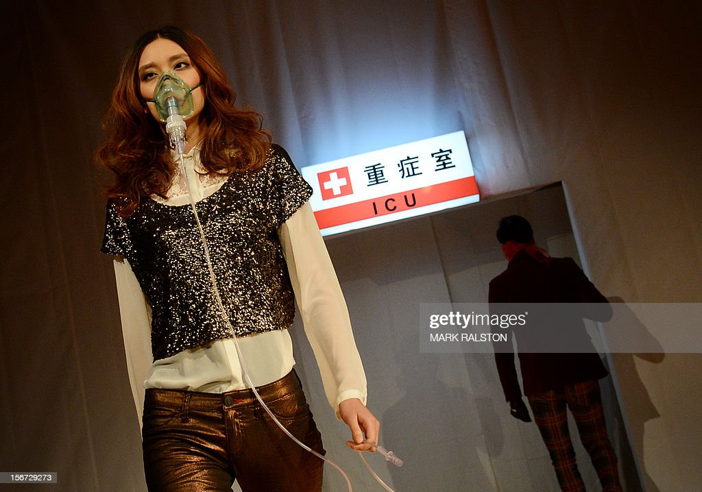 A model wears a face mask during the 'Toxic Threads - The Big Fashion Stitch-up' fashion parade organized by environment action group Greenpeace to highlight chemical contamination in the fashion industry, in Beijing on November 20, 2012. Greenpeace released the results of a months-long global investigation into some of the world's top-selling fast fashion houses, with sample products purchased from nearly 30 countries. According to Greenpeace, nearly two thirds of the clothing tested positive for hormone-disrupting and dyes that release cancer-causing substances. AFP PHOTO/Mark RALSTON