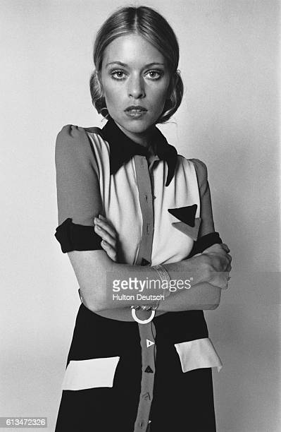 A model wears a frontbuttoning dress with square shoulders and triangular trimmings August 1970