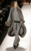 A model wears a gray cashmere purl sweater coat with fox trim gray cashmere purl turtleneck sweater gray cashmere flannel pant black studded leather...