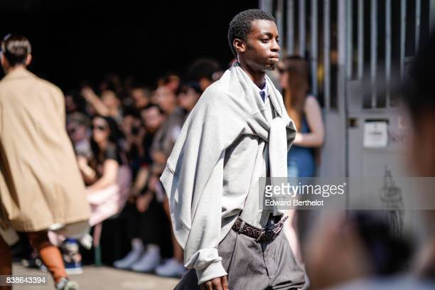 A model wears a gray pull over and a gray shirt outside the Y/Project show during Paris Fashion Week Menswear Spring/Summer 2018 on June 21 2017 in...