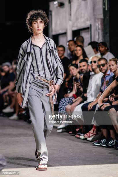 A model wears a gray striped top gray pants a belt sandals outside the Y/Project show during Paris Fashion Week Menswear Spring/Summer 2018 on June...