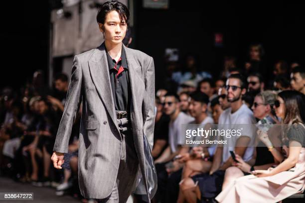 A model wears a gray suit a black shirt outside the Y/Project show during Paris Fashion Week Menswear Spring/Summer 2018 on June 21 2017 in Paris...