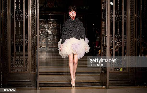 A model wears a jewelled headpiece by Lara Jensen as she walks on the catwalk during the Inbar Spector presentation at London Fashion Week in central...
