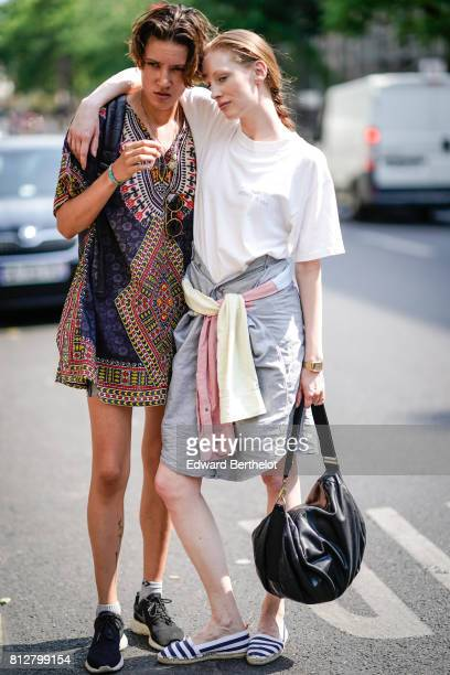 A model wears a multicolor pattern short dress black sneakers a model wears a white tshirt a gray skirt striped shors a black leather bag outside the...