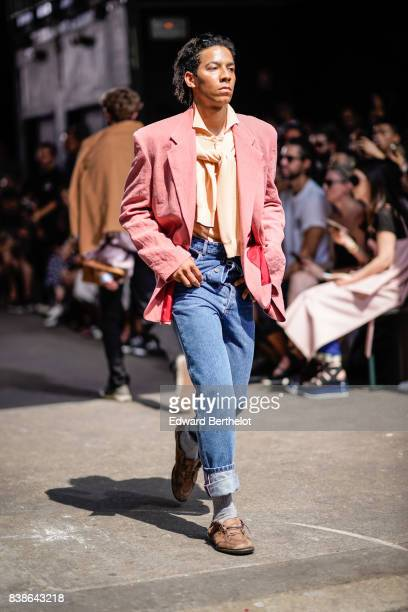A model wears a pink suit jacket an orange shirt blue cropped jeans gray socks brown shoes outside the Y/Project show during Paris Fashion Week...