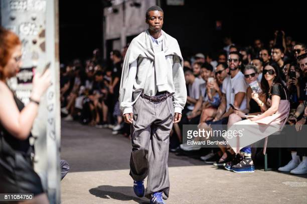 A model wears a pull over blue sneakers gray large pants outside the Y/Project show during Paris Fashion Week Menswear Spring/Summer 2018 on June 21...