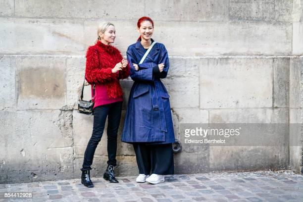 A model wears a red pull over a model wears a blue rain coat outside Koche during Paris Fashion Week Womenswear Spring/Summer 2018 on September 26...