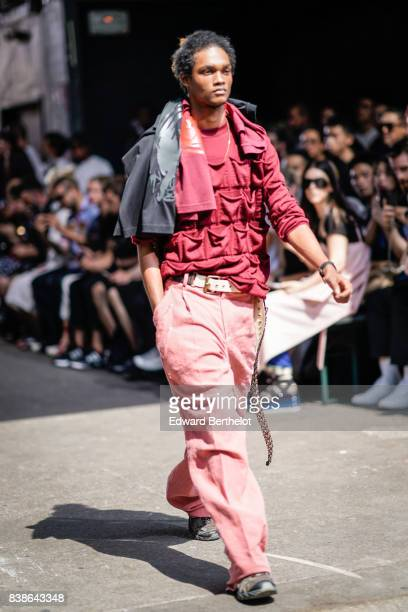 A model wears a red top a belt pink pants outside the Y/Project show during Paris Fashion Week Menswear Spring/Summer 2018 on June 21 2017 in Paris...