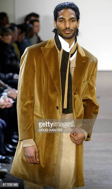 A model wears a sandstone velour overcoat camel henley shirt white pique shirt granite suede pant natural laceup boot with toe seam camel and brown...