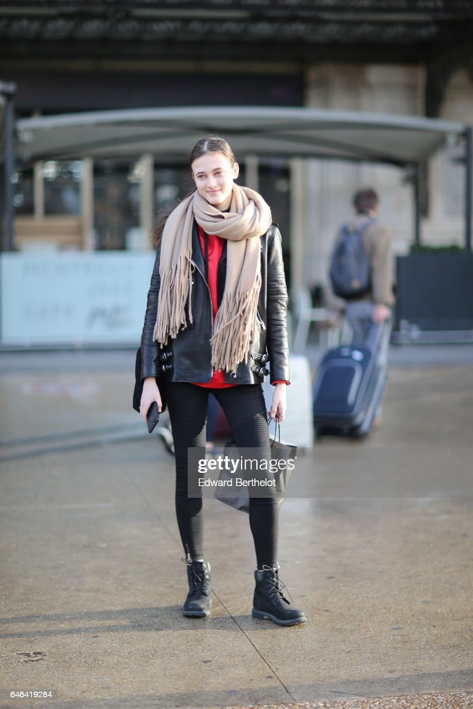A model wears a scarf, a red top, and a black leather jacket, outside the Olivier Theyskens show, during Paris Fashion Week Womenswear Fall/Winter 2017/2018, on February 28, 2017 in Paris, France.