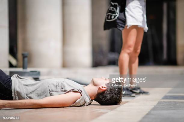 A model wears a sleeveless top and lays on the floor outside the 22/4 Hommes show during Paris Fashion Week Menswear Spring/Summer 2018 on June 23...