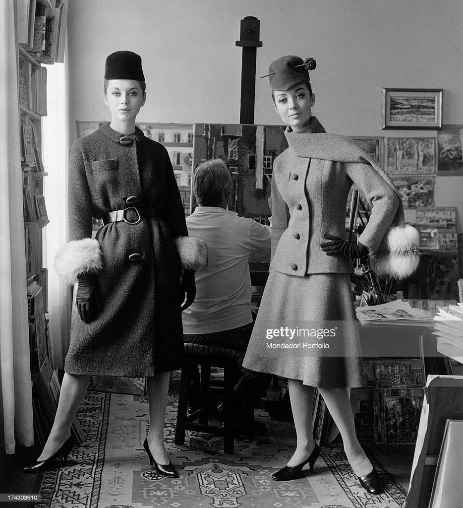A model wears a typical of Roberto Capucci suit in heavy gabardine green; the jacket clings to the bust due to some cuts that intersect at the waist, the skirt is knee-length, and the sleeves end just above the wrist. Italy, 1962..