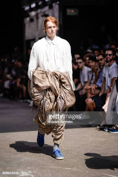 A model wears a white shirt brown ruffled pants blue sneakers shoes outside the Y/Project show during Paris Fashion Week Menswear Spring/Summer 2018...