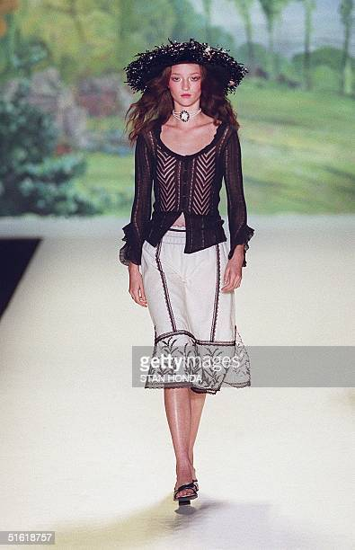 A model wears a wide brim hat with a longsleeve sheer black top over a white print skirt during the Anna Sui fashion show 15 September 1999 at the...