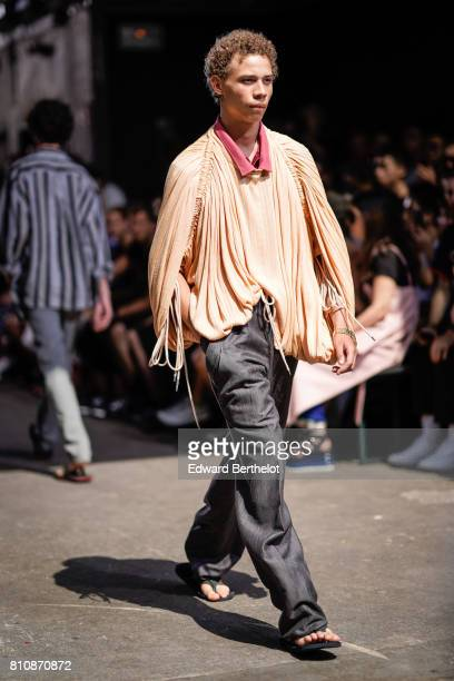A model wears a yellow fringe pull over black pants sandals outside the Y/Project show during Paris Fashion Week Menswear Spring/Summer 2018 on June...