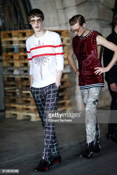 A model wears clear sunglasses a white pull over with red lines checkered pants outside the Icosae show during Paris Fashion Week Menswear...