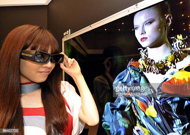 A model wears special 3D glasses while watching the new 3D LCD panel for 60inch sized televisions unveiled by Japanese electronics company Sharp in...