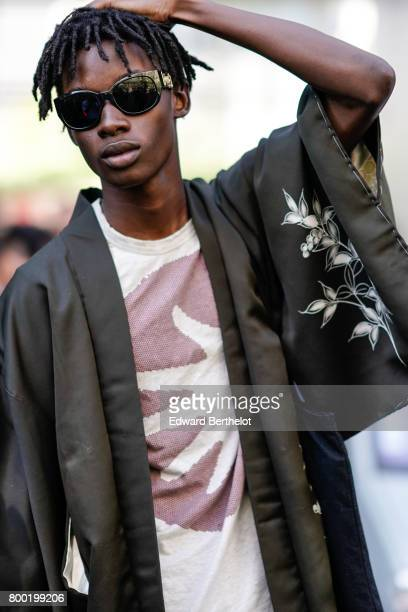 A model wears sunglasses a silk kimono with flower prints after the CDG Comme des Garcons show during Paris Fashion Week Menswear Spring/Summer 2018...