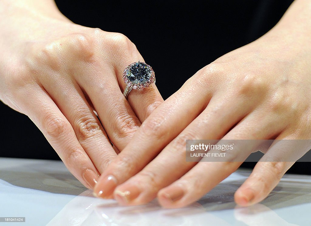 A model wears the world's largest flawless fancy vivid blue diamond ring during a media preview at Sotheby's auction house in Hong Kong on September 19, 2013. The ring is expected to achieve a sale in excess of 19 million USD and will go under the hammer in Hong Kong on October 7. AFP PHOTO / Laurent FIEVET
