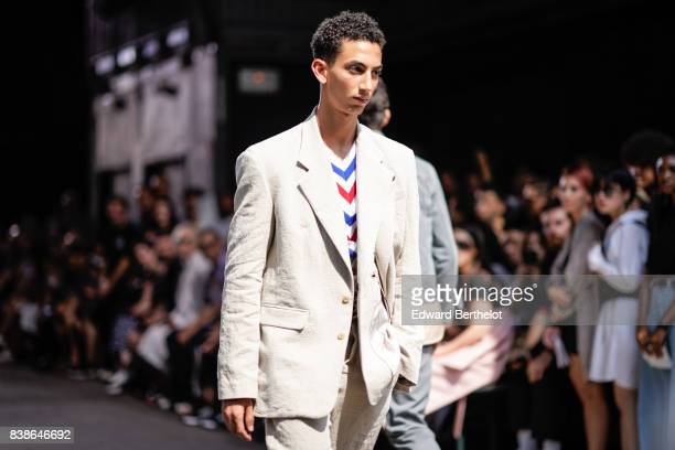 A model wears white suit outside the Y/Project show during Paris Fashion Week Menswear Spring/Summer 2018 on June 21 2017 in Paris France