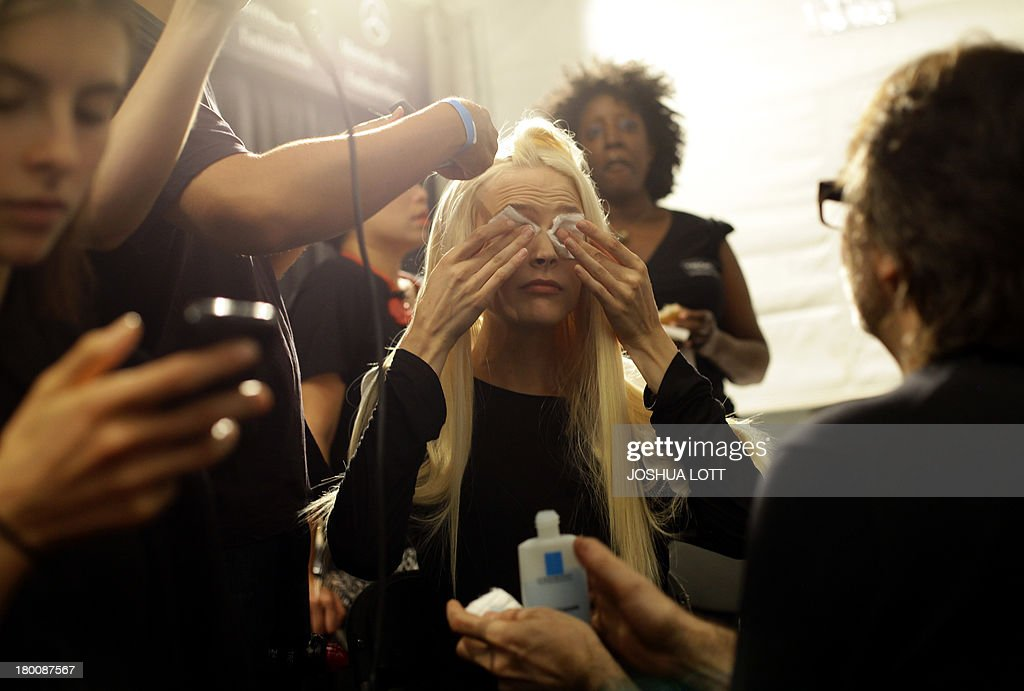 A model wipes make-up from her eyes as her is styled before the Vivienne Tam runway show during the Mercedes-Benz Fashion Week Spring 2014 collections on September 8, 2013 in New York. AFP PHOTO/Joshua Lott