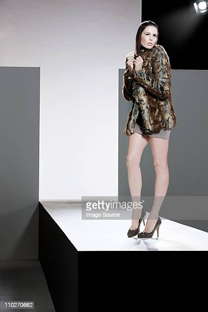 Model with fur coat on catwalk at fashion show