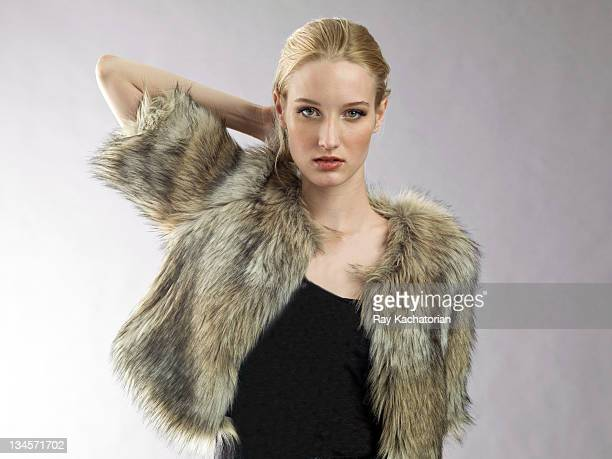 Model with hand behind head wearing fur coat
