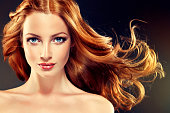 Young, red haired woman  with voluminous, shiny and wavy hair . Beautiful model with long, dense and curly hairstyle.