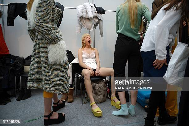 TOPSHOT A model yawns as she awaits backstage before presenting creations by finalists of the Russian Silhouette young designers contest during the...