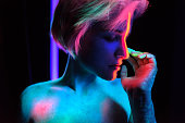 Young beautiful girl model with short haircut in the studio on a black background. Neon paints, makeup, body painting, colored hair coloring, creative color, poses in the light of soffits. Hands, face