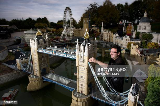 Modelmaker Giorgio Pastero places hundreds of LEGO minifigure ghosts on a LEGO model of London's Tower Bridge during a photocall at Legoland in...