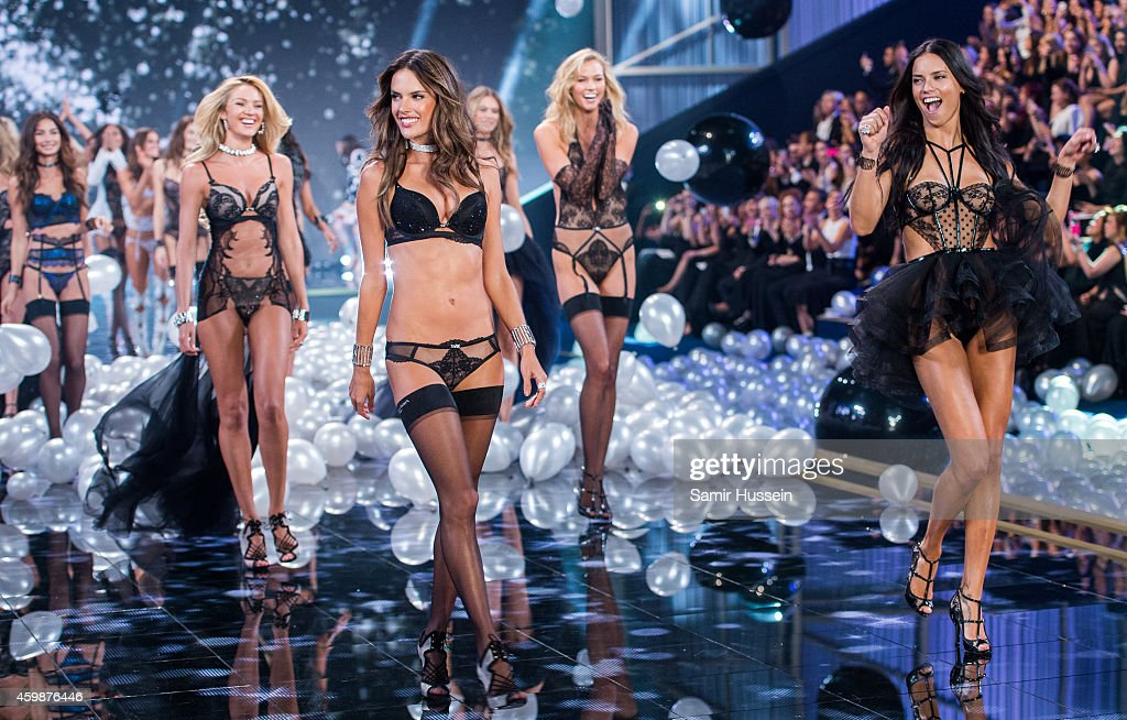 Models Adriana Lima (R) and Alessandra Ambrosio lead out the models as they walk the runway at the annual Victoria's Secret fashion show at Earls Court on December 2, 2014 in London, England.