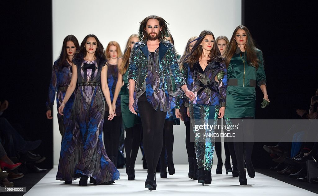 Models and designer Marcel Ostertag (C) present a creation by designer Marcel Ostertag during the Autumn/Winter 2013 shows of the Mercedes-Benz Fashion Week on January 17, 2013 in Berlin. The Berlin Fashion Week takes place from January 15 to 20, 2012.