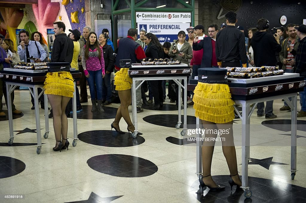 Models appearing as if cut in half during a magic show, offer cookies to the commuters of the subway in Santiago, on July 29,2014.
