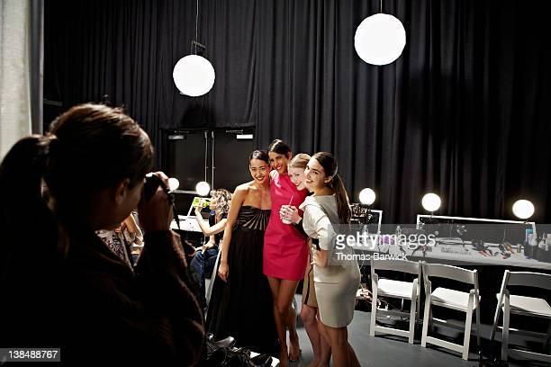 Models backstage at fashion show taking photo