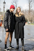 Models Binx Walton and Anna Ewers exit the Chanel show at Grand Palais on March 07 2016 in Paris France Binx wears a red beanie hat with an all black...