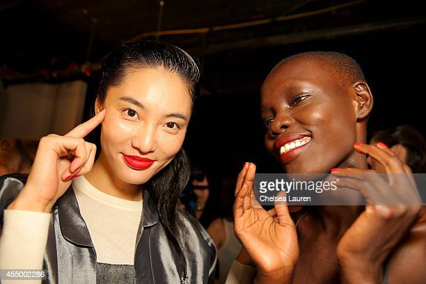 Models Bonnie Chen and Grace Bol prepare backstage at the Zac Posen fashion show during MercedesBenz Fashion Week Spring 2015 on September 8 2014 in...
